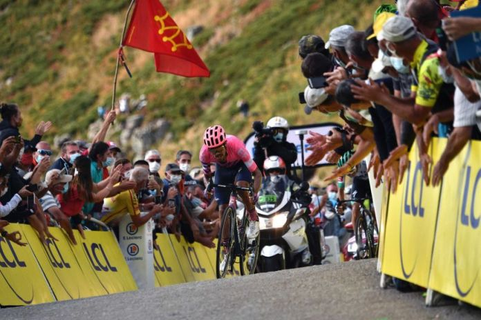 A cyclist in a pink shirt and helmet climbs a steep incline to the finish of a Tour de France stage.