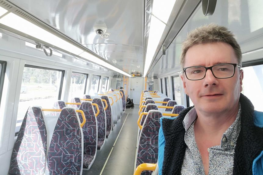 Man in glasses stands in an empty carriage on a Brisbane train
