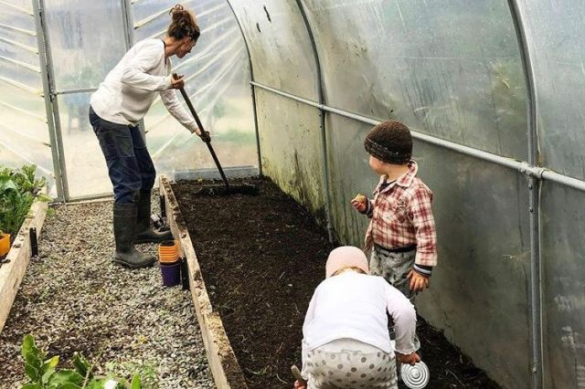 woman and two small children gardening
