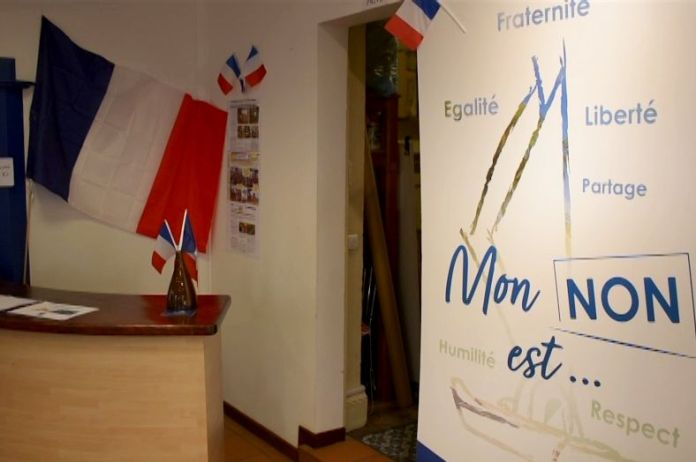 In a dimly lit reception area, you see a lot of French flags with a large sign that reads 'mon non est'.
