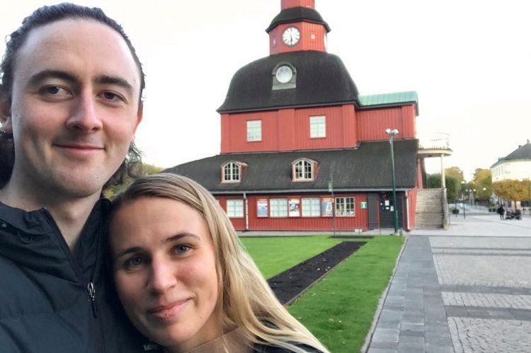Ethan Brooker and his partner stare at the camera and embrace in a selfie taken in front of a big old red building.