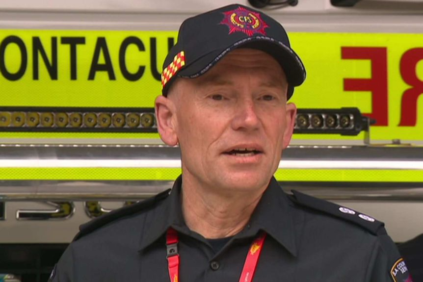 A man in a CFS hat and uniform in front of a fire truck (centre) with another man in a collared shirt.