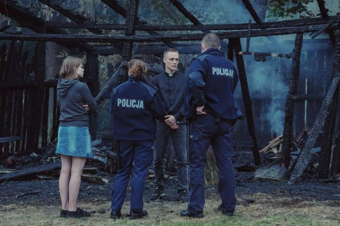A scene from the film Corpus Christi with a young priest speaking to the police in front of a burned building