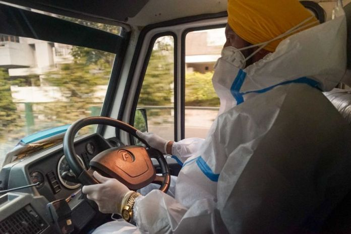 A Sikh Indian in full PPE behind the wheel of a car