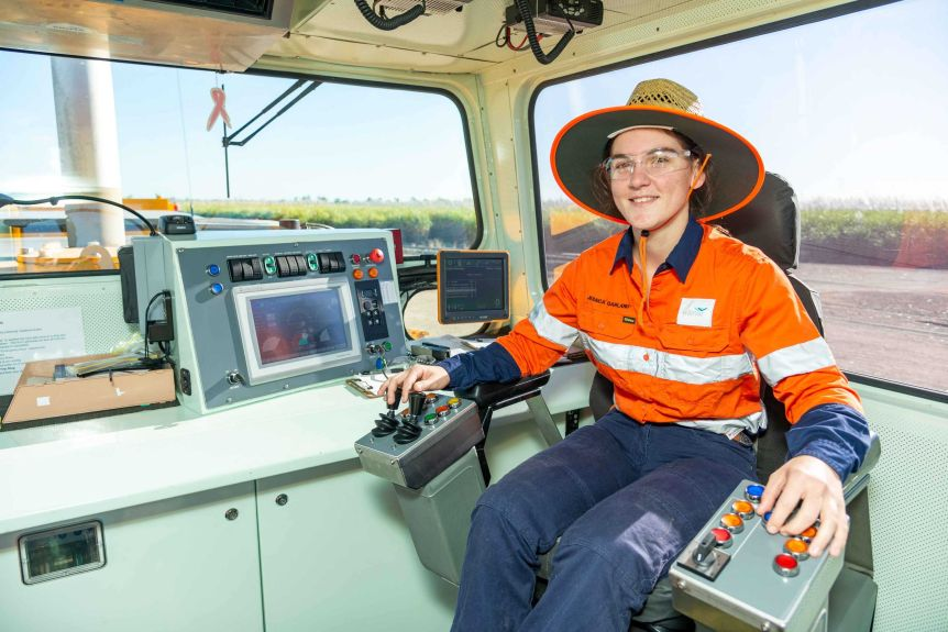 a young woman sits in the control area of a cane train