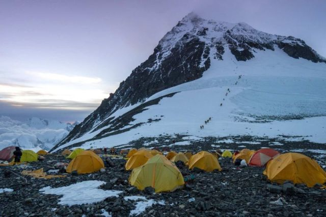 Yellow tents with a snow-covered mountain rising up behind them.