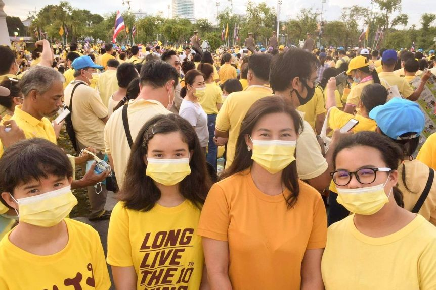 A woman with three girls wearing masks and yellow shirts stand in front of a crowd of people wearing yellow.
