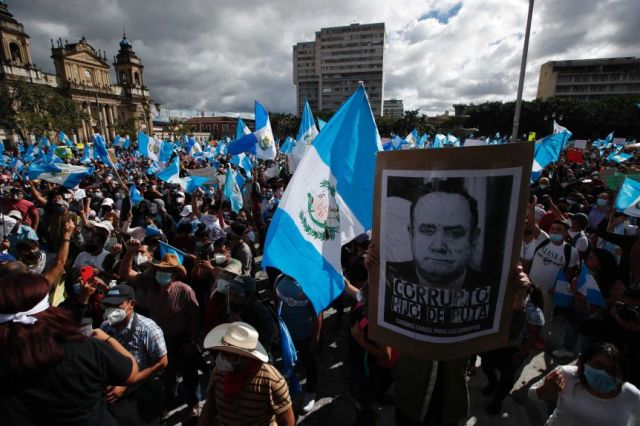 Protesters gather outside Congress in Guatemala City with flags and placards