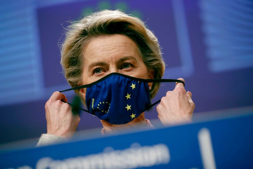 Ursula von der Leyen pulls a blue face mask with the EU symbol on it across her mouth.