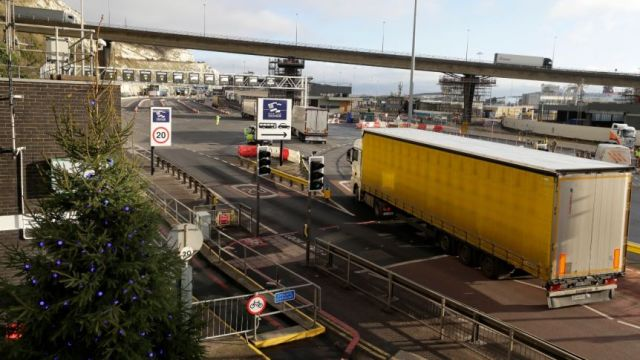 a truck is seen at the entry of the port of dover with other trucks ahead on a bridge
