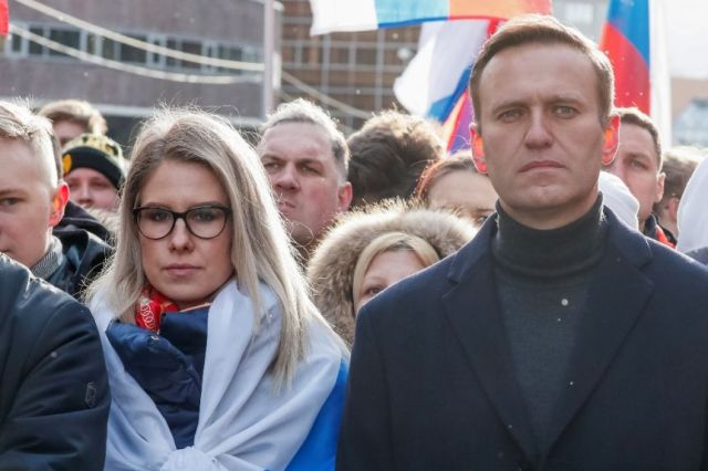 Lyubov Sobol and Alexei Navalny standing next to each other at a rally looking at the camera