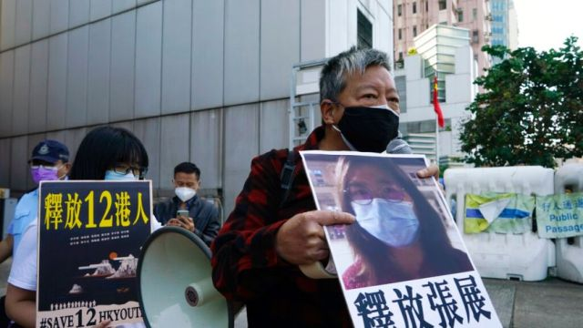 Pro-democracy activists old placards with the picture of Chinese citizen journalist Zhang Zhan as they march.
