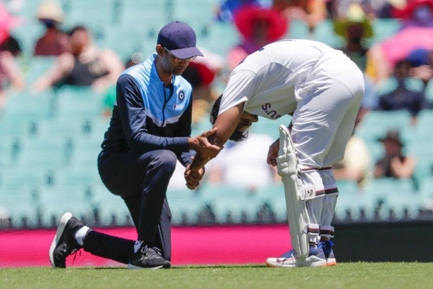 Rishabh Pant bends over and holds his left arm out straight as another man looks at it