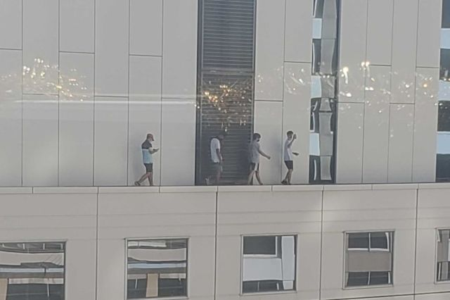 Four boys walk on ledge of a high-rise