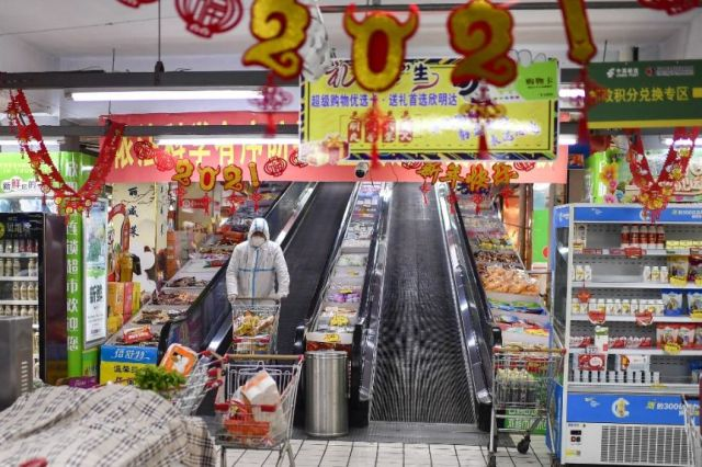 You view a lone person in full PPE, pushing a trolley in a supermarket littered with signs celebrating the Lunar New Year.