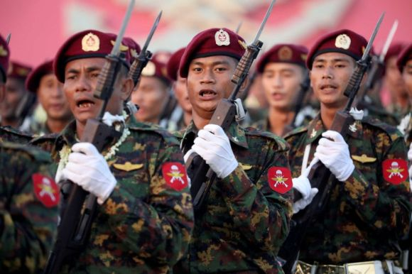 A group of soldiers carrying bayonets while wearing maroon berets