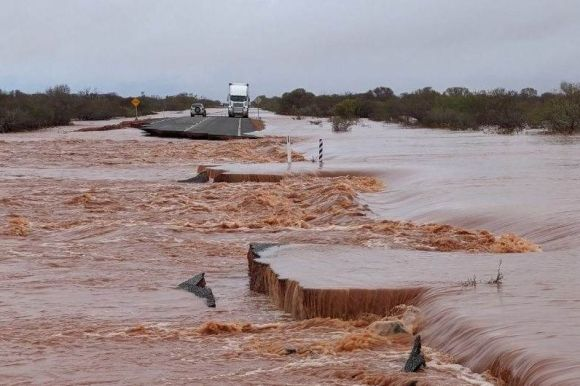 Raging floodwaters with trapped vehicles on an island.