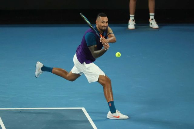 Nick Kyrgios grimaces as he hits a double-handed backhand