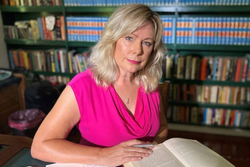 Christine Smyth sits in a office desk with book in front of her and library shelves of books behind him.