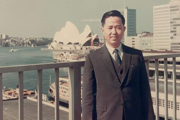 A young Chinese man outside the Sydney Opera House.