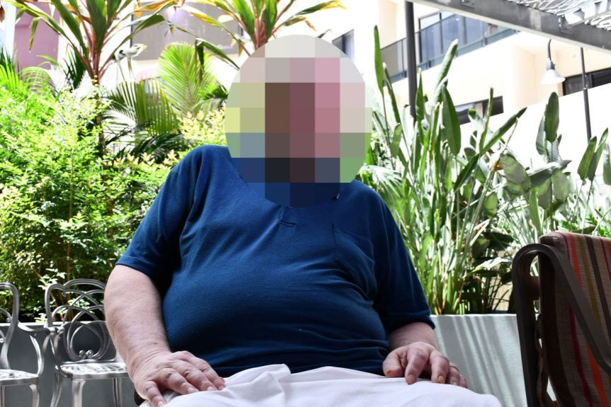 A man sits in a garden outside a city building, his face blurred to protect his identity.