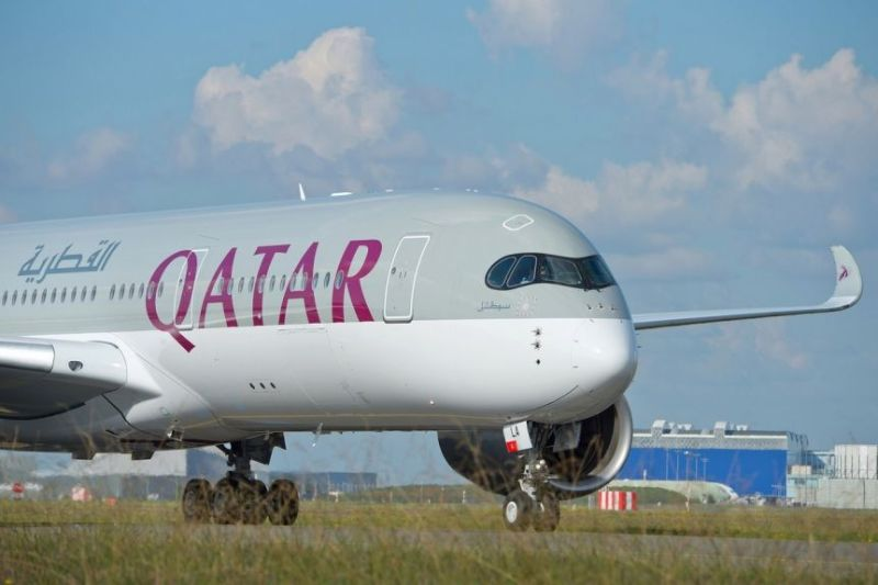 A Qatar Airways Airbus A350-900 on the tarmac on a lightly cloudy day.