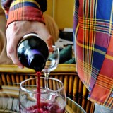 Glass of purple wine being poured.
