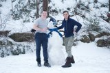 Matt Roberts and Ben Lisson standing next to snowman wearing ABC hat and with ABC News microphone as nose.
