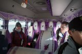 Inside bus with purple seats, tassles on window edges and toilet roll hanging from hand rail on roof.