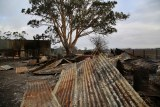 Sheets of corrugated iron and debris lie on burnt ground at a farm.