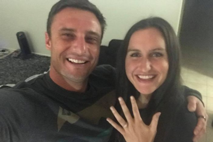 A man and woman pose for a selfie for their engagement