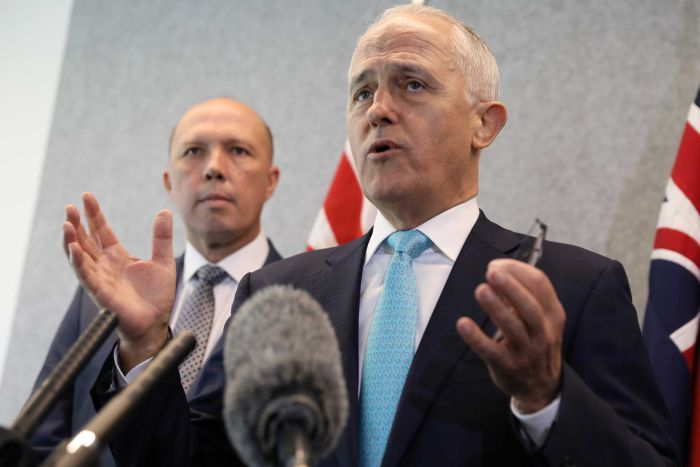 Malcolm Turnbull gestures at the microphone while Peter Dutton stares at him from behind.