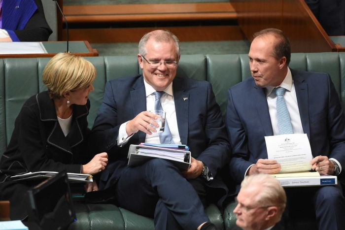 Scott Morrison smiles as Julie Bishop and Peter Dutton turn towards him to speak.