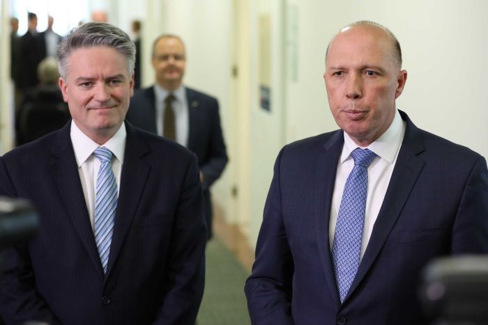 Mathias Cormann grimaces while Peter Dutton speaks beside him. Both men look disapointed.