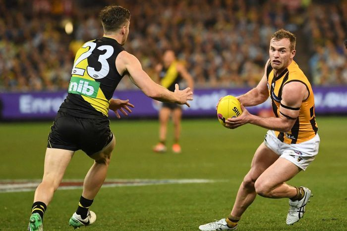 Tom Mitchell with the ball as he tries to beat the defence of Kane Lambert.