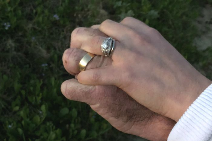 Man and woman's hands joined, wearing wedding rings
