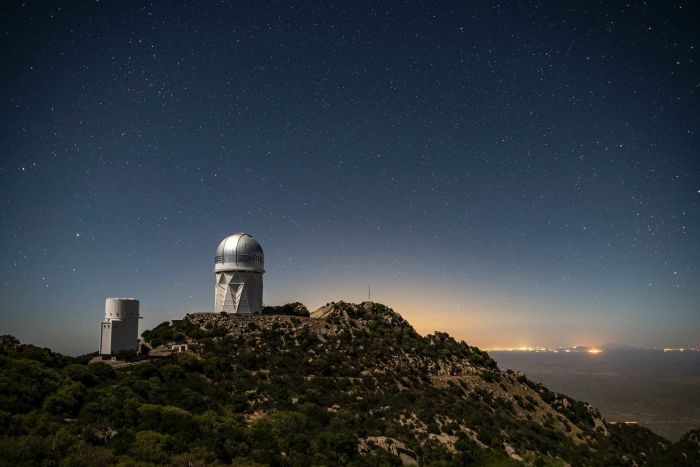 An Observatory and the sky with a city in the background.