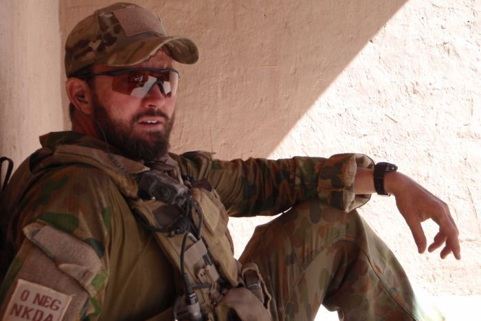 a commando wearing a hat and sunglasses