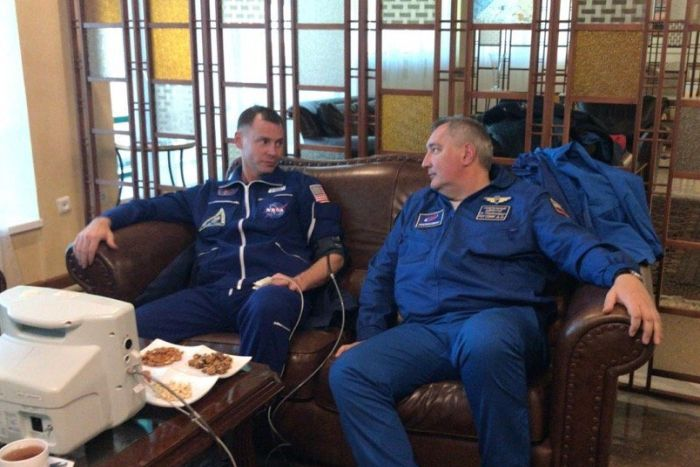 Astronauts Nick Hague and Alexei Ovchinin relax on a sofa as they undergo tests following the rocket emergency landing.