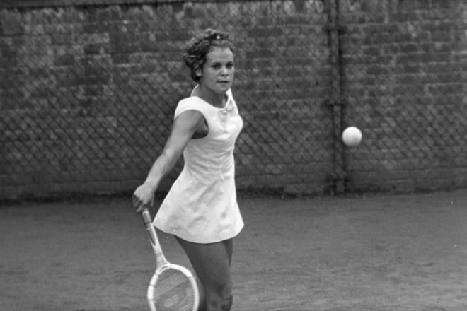 A black and white photo of a young woman staring at a tennis ball that she is about to hit.