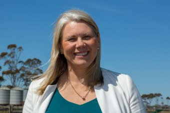 Kate Roffey is in front of a paddock and the shed near Werribee.