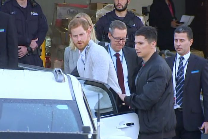 Prince Harry getting into a car with police in the background