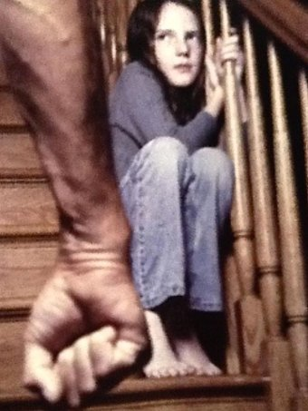 A young girl cowers on a stair case with a man's fist in the foreground