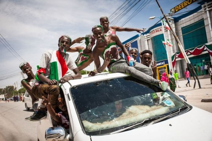 Men painted in colours of Somaliland's flag stick their head out of a car. They are smiling and exuberant.