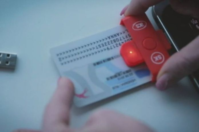 A white credit card sized card with numbers and letters is inserted into a reader attached to a smart phone