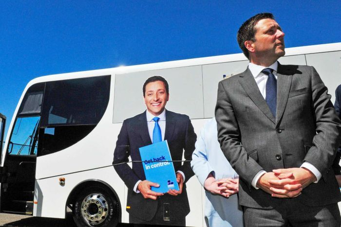 A bus bearing an image of Opposition Leader Matthew Guy and the words 'Get Back in Conrtol' is shown parked on the street.