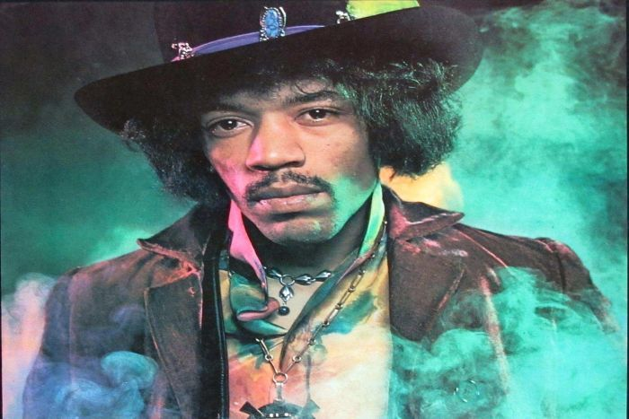 Portrait of Hendrix in elaborate dress with green smoke swirling behind