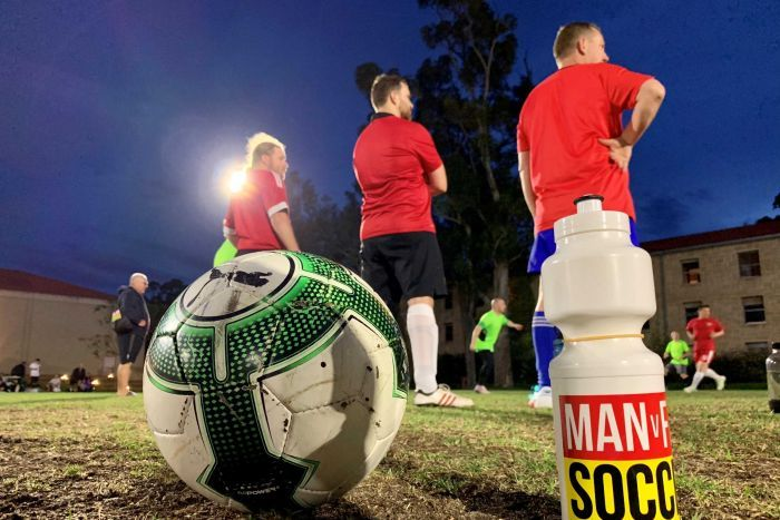Drink bottle and soccer ball on a soccer pitch