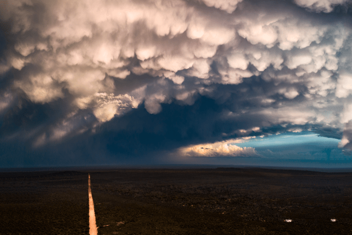 A dirt road is lit up by sun shining through storm clouds.