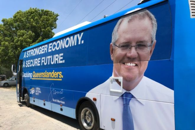 A blue bus with the prime minister's face on the back and political slogans written across the windows